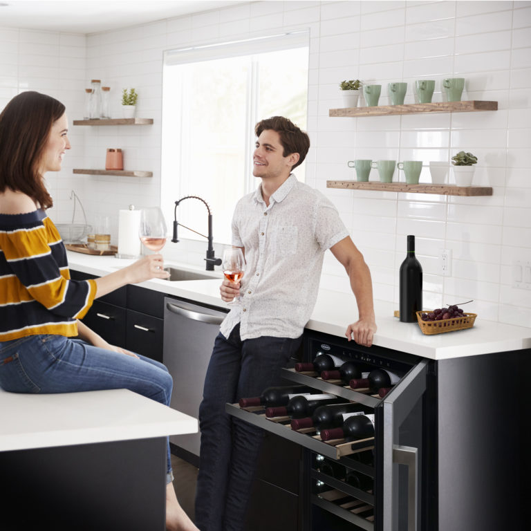 Couple Making Drinking Wine At Home Sitting On Kitchen Island